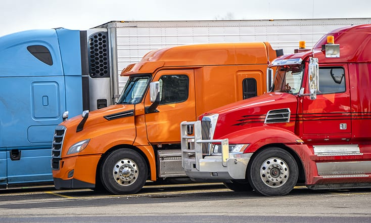 Big rigs commercial cargo haulers Semi Trucks with different semi trailers of various brands and models stand on truck stop parking for truck drivers rest and continue delivery routes as scheduled